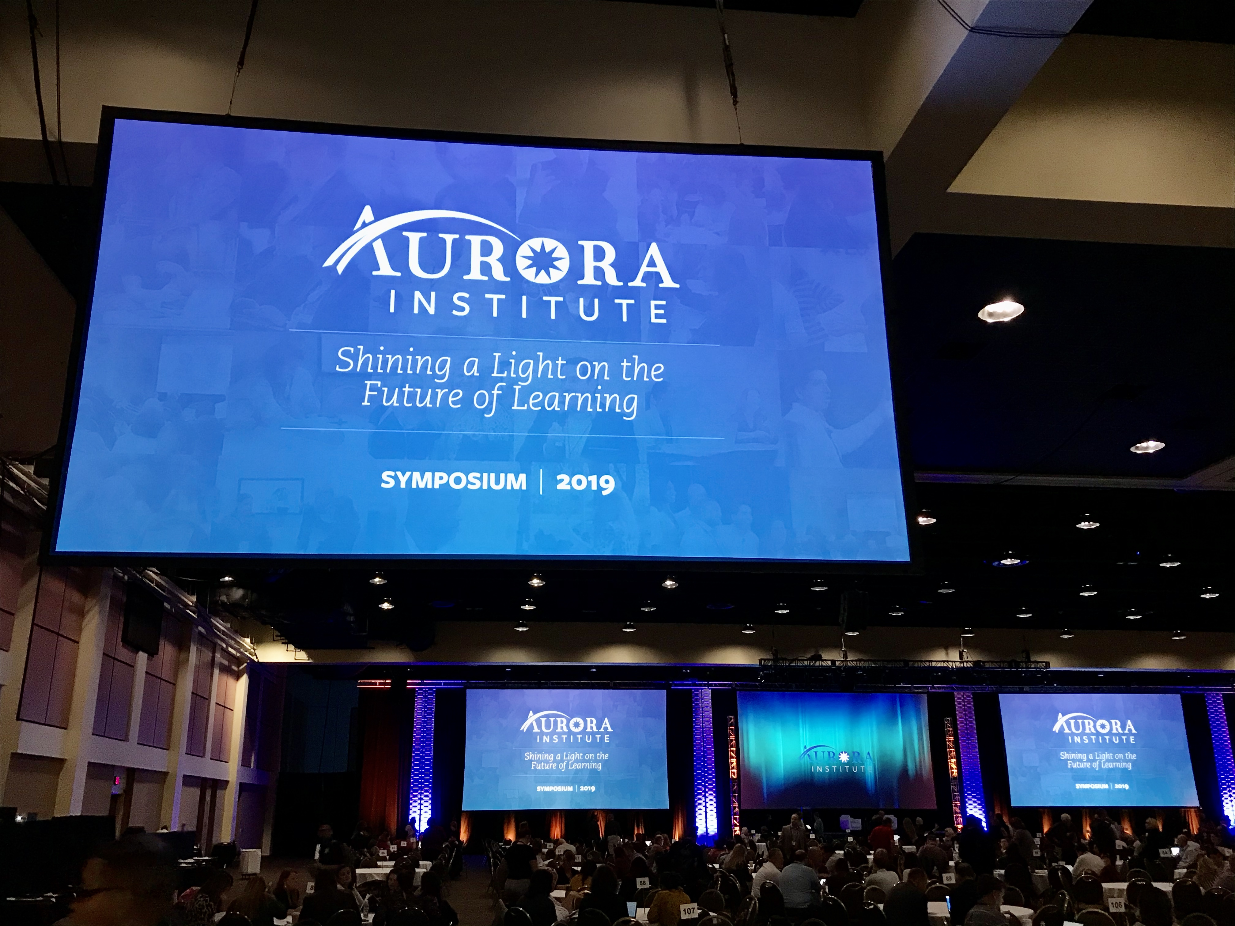 """Photo of a screen that says """"Aurora Institute: Shining a Light on the Future of Learning Symposium 2019"""""""