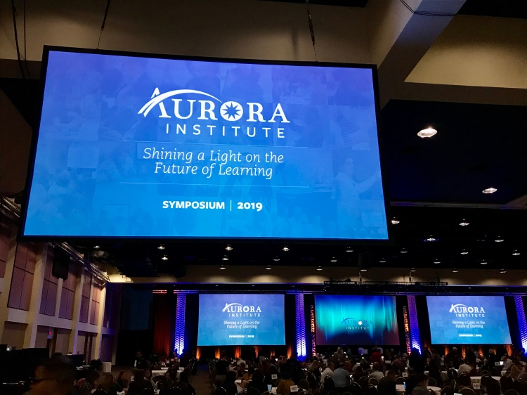 "Photo of a screen that says ""Aurora Institute: Shining a Light on the Future of Learning Symposium 2019"""