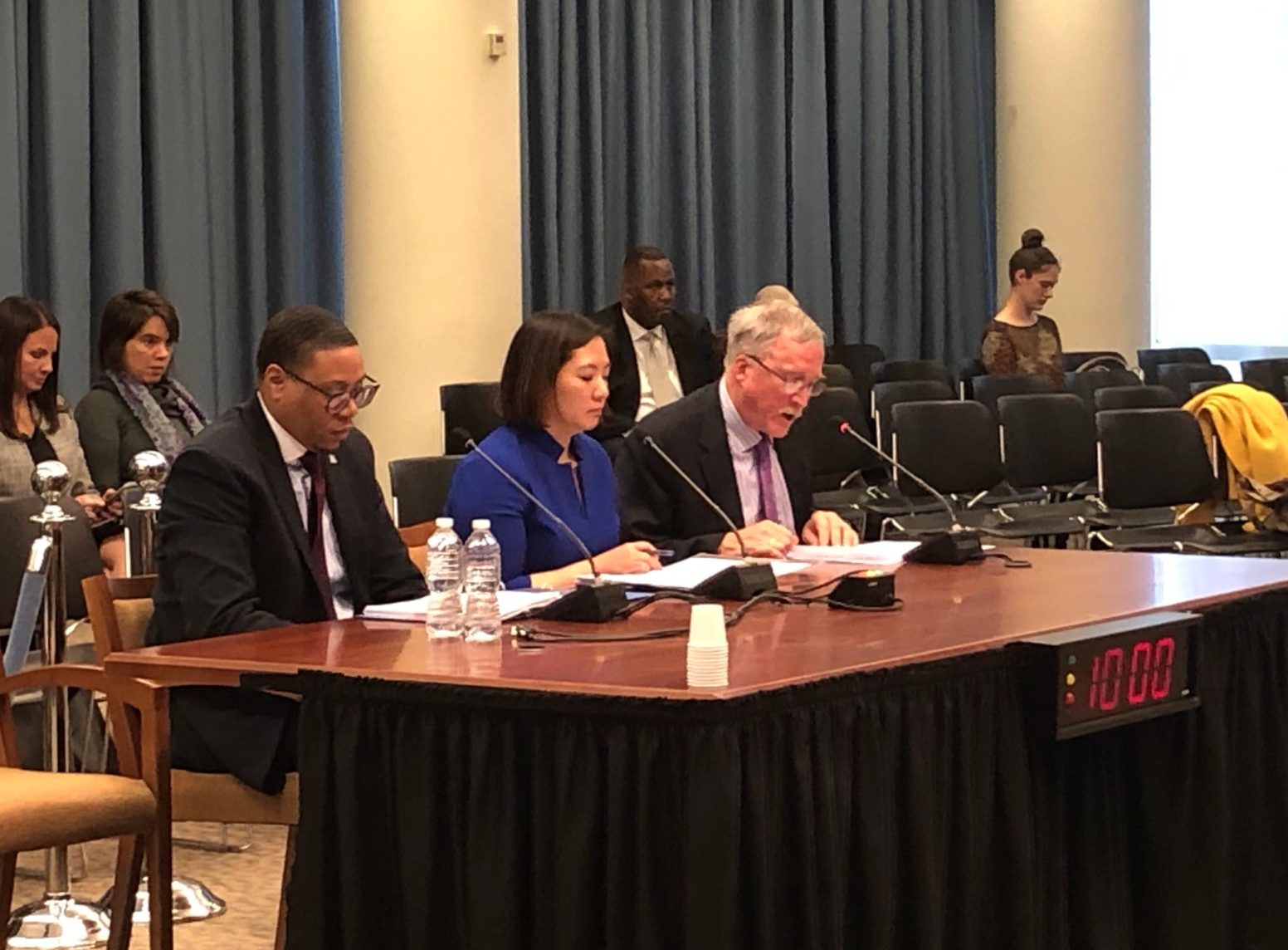 Ward 4 Representative, Frazier O'Leary, testifying before Council on teacher attrition. He is seated at a table, speaking into a microphone, and is seated next to state superintendent, Hanseul Kang, and DC public schools chancellor, Dr. Lewis Ferebee.
