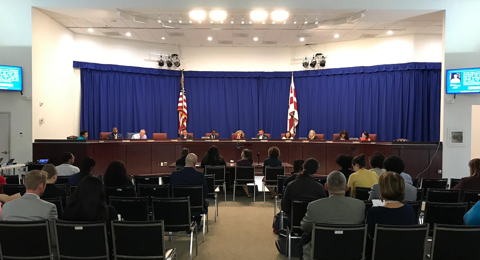 A picture of one of the State Board's monthly public meetings. The members of the state board are seated at the dais and members of the public are seated in rows.